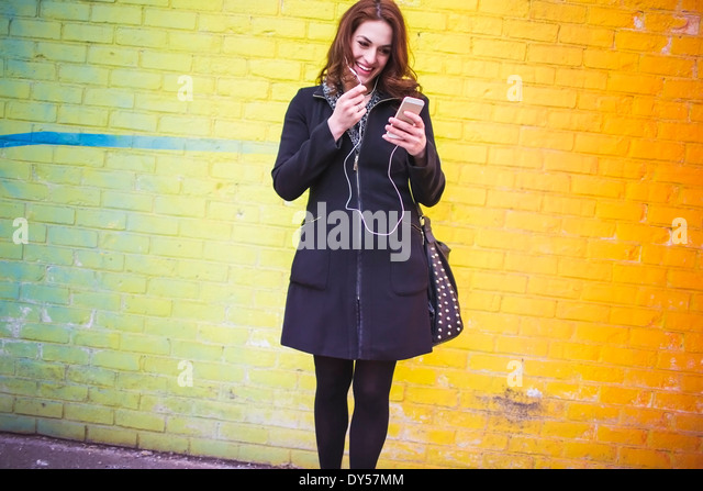 Young woman choosing music on city street - Stock Image