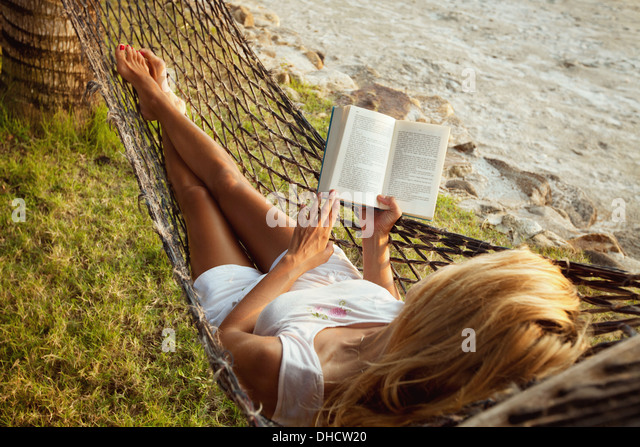 Woman lying in a hammock on the beach and enjoying a book reading - Stock Image