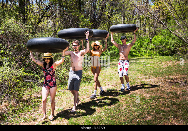 Four people carrying inner tubes above heads - Stock Image