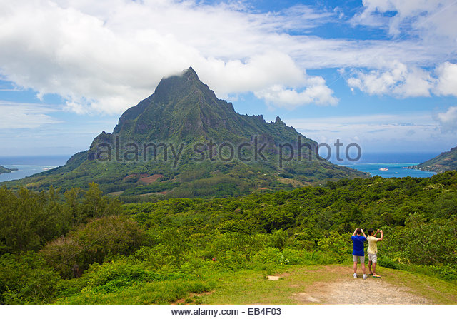 Tourist taking photos at Le Belvedere Lookout, overlooking Opunohu Bay and Cook Bay, and the Opunohu Valley. - Stock Image