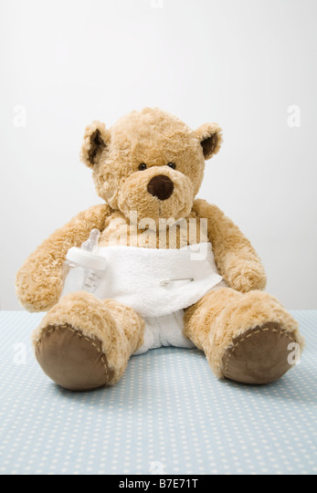 Teddy bear in a diaper - Stock Image