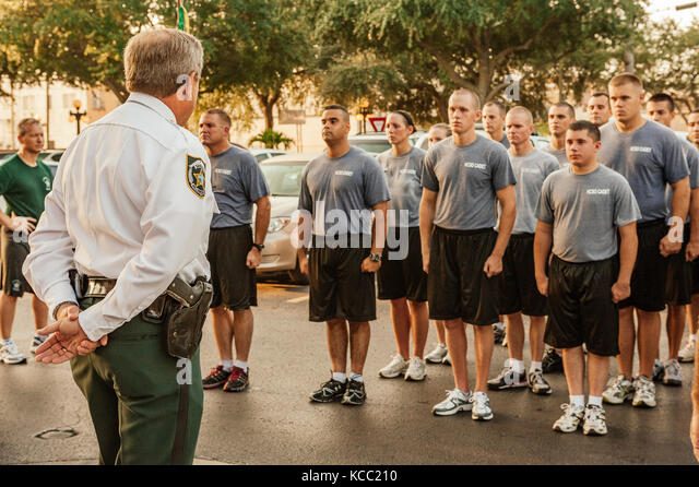Police, law enforcement recruit class standing in formation addressed by command officer after training run through - Stock Image