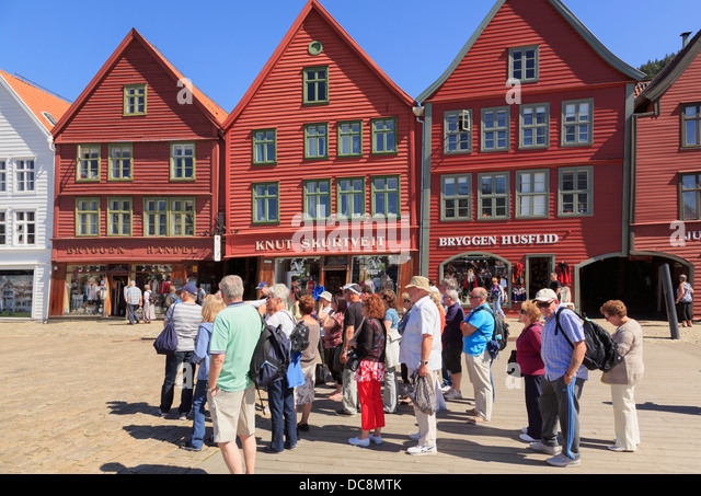 Tourists group by 14th century medieval wooden Hanseatic buildings on waterfront in old harbour district of Bryggen, - Stock Image