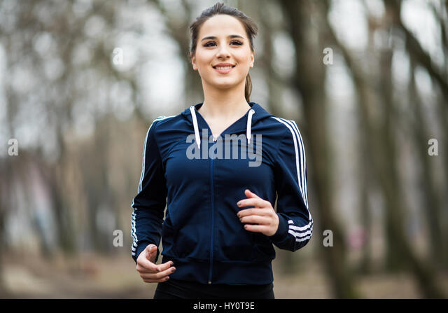 Young woman running and training in autumn nature - Stock Image