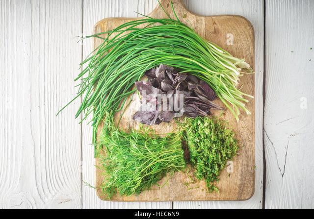 Basil, onion, dill on cutting board horizontal - Stock Image