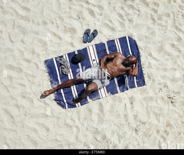 Top view of young guy lying shirtless on a mat reading a magazine. African male model relaxing on beach. - Stock Image