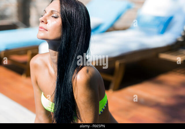 Beautiful woman with closed eyes sunbathing at the poolside - Stock Image