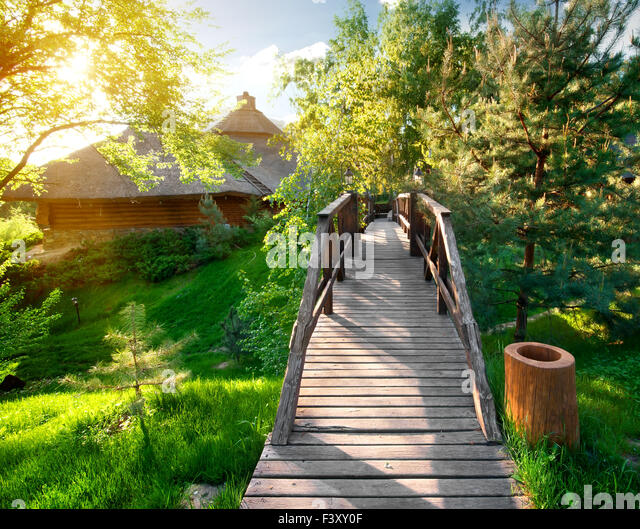 Decorative bridge near pines and wooden houses - Stock Image