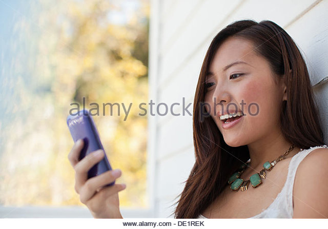 Smiling woman using cell phone outdoors - Stock Image