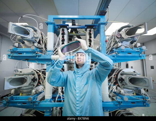 Scientist inspecting laser lens - Stock Image