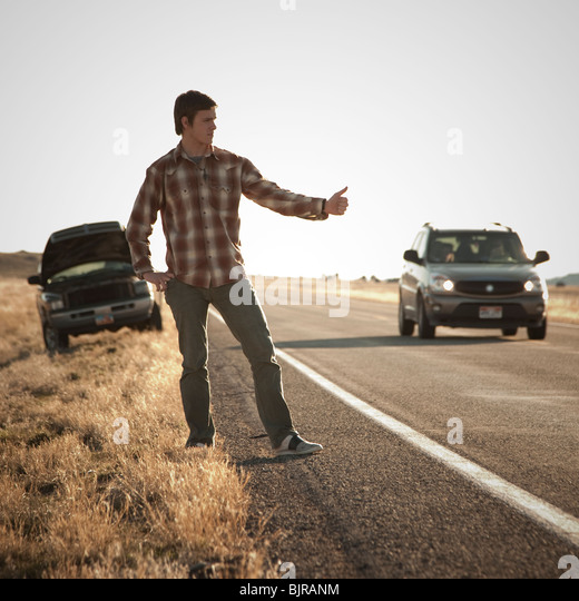 USA, Utah, man hailing on roadside, broken car in background - Stock Image