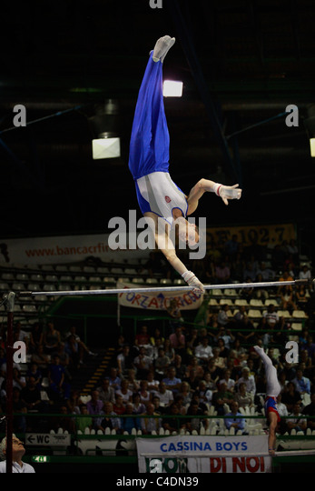 gymnastics competition: a gymnast's performing his high bar routine - Stock Image