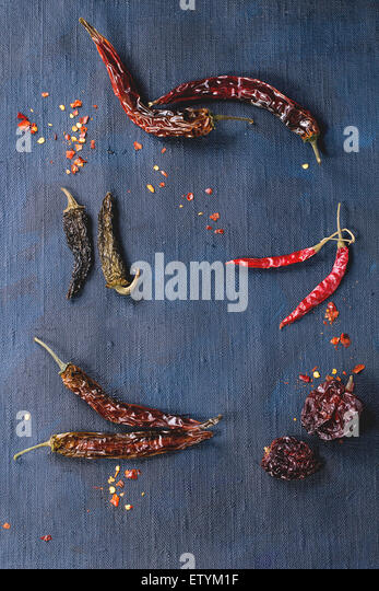 Assortment of dryed whole and flakes red hot chili peppers over dark blue canvas as background - Stock Image