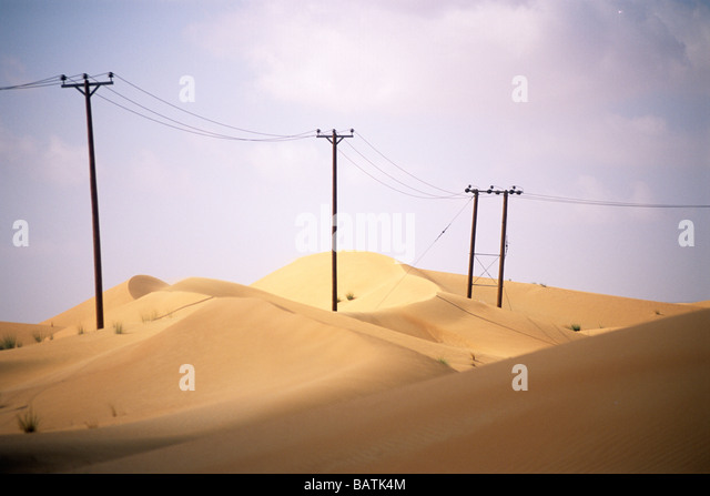 Wooden pylons supporting powerlines acrosss and dunes. The voltage transmitted in powerlines supported by wood. - Stock Image
