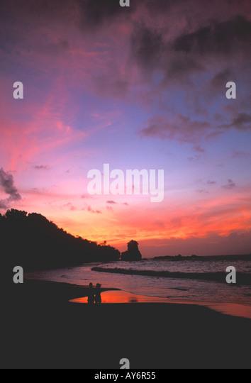 Tropical sunset couple standing on beach silhouette rocky shoreline coast coastline - Stock Image