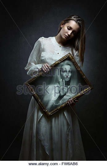 Young woman soul imprisoned inside magical mirror . Dark fantasy and surreal - Stock Image