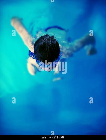 Boy swimming in blue water. - Stock-Bilder