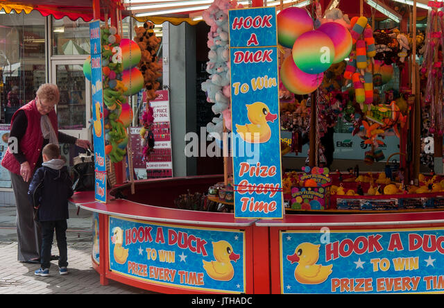 Melton Mowbray 9th August 2017: Rain showers, wind and clear spells in the town center with sand and fun fair entertianment. - Stock Image