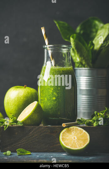Green smoothie in bottle with apple, romaine lettuce, lime, mint - Stock Image