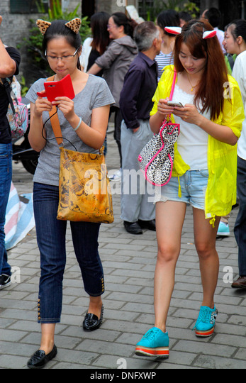 Beijing China Dongcheng District Nanluoguxiang hutong historic shopping Asian teen girl friends smartphone texting - Stock Image