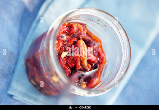 Jar of stewed red pepers in oil and garlic - Stock-Bilder
