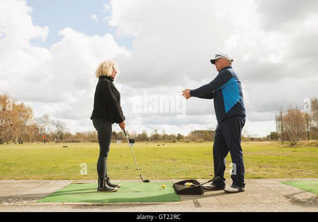 Man assisting woman in playing golf at driving range - Stock-Bilder