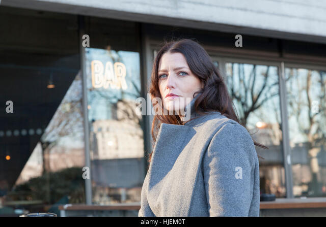 Attractive tall woman outside a bar - Stock Image