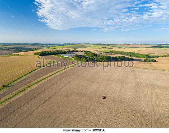 Aerial View Of Tractor Pulling Drill Sowing Seed In Field - Stock Image