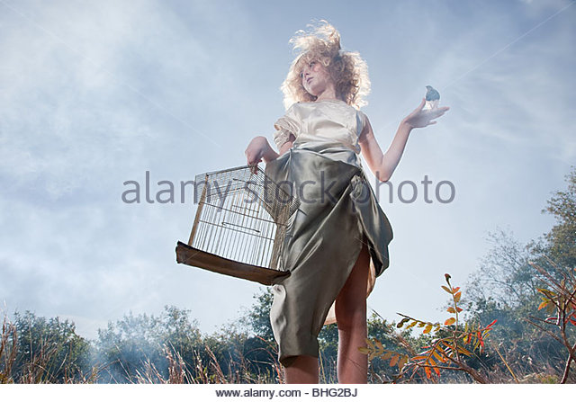 Girl with a bird and cage - Stock Image