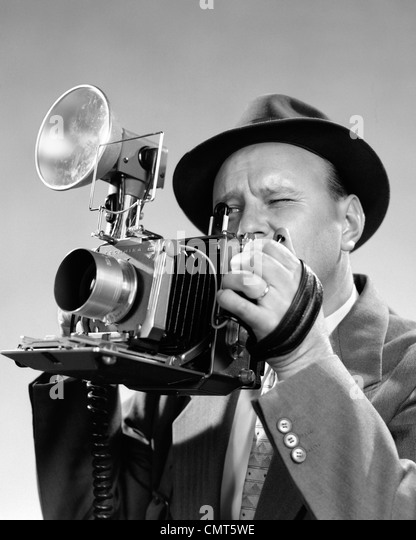 1950s PORTRAIT OF PHOTOGRAPHER MAN IN SUIT AND FEDORA HAT SQUINTING EYE TO LOOK THROUGH VIEWFINDER OF PRESS CAMERA - Stock Image
