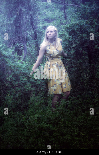 a blond girl with a yellow dress in the woods - Stock Image
