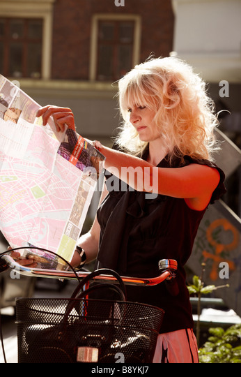 A woman on a bike using a map Copenhagen Denmark. - Stock Image