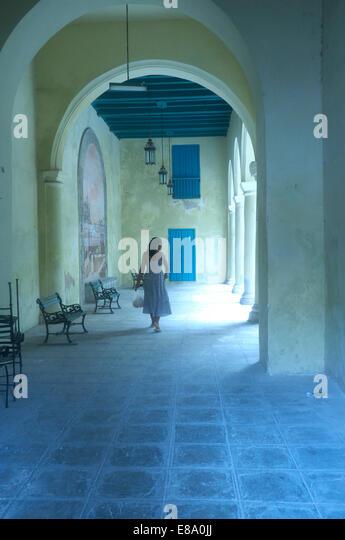 Woman walking through a portico, Havana, Cuba - Stock Image