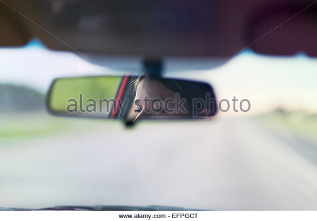 Reflection of woman's eyes on rearview mirror of vehicle - Stock Image