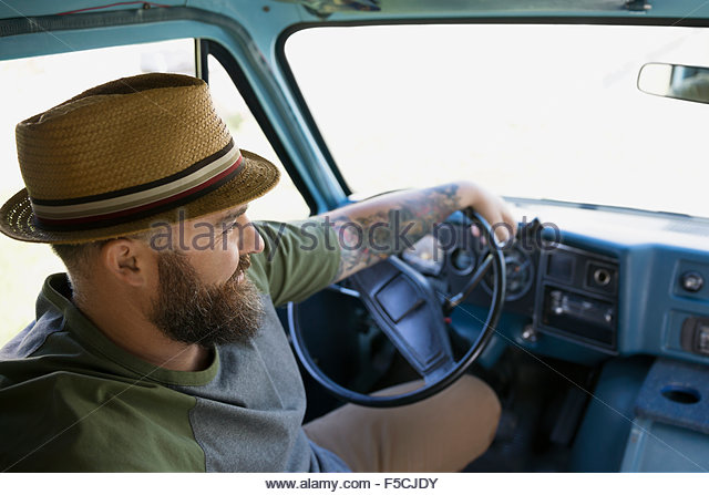 Bearded man in hat driving van - Stock Image