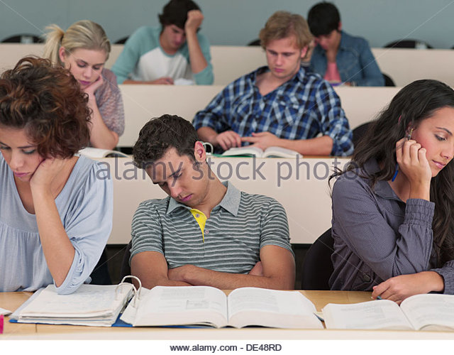 Bored college students sleeping in lecture hall - Stock Image