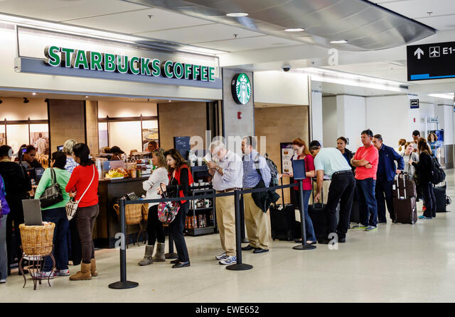 Miami Florida International Airport MIA inside terminal concourse gate area Starbucks Coffee line queue customers - Stock Image