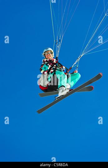 A female paraglider pilot smiles whilst flying past. - Stock-Bilder
