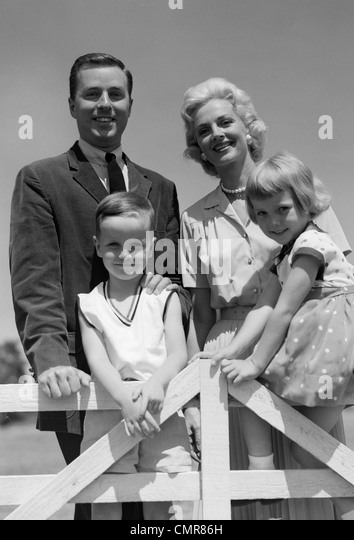 1950s 1960s PORTRAIT SMILING FAMILY FATHER MOTHER SON DAUGHTER BEHIND WHITE FENCE OUTDOOR - Stock Image