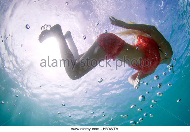 underwater view of a young girl swimming in a red lace cover up - Stock Image