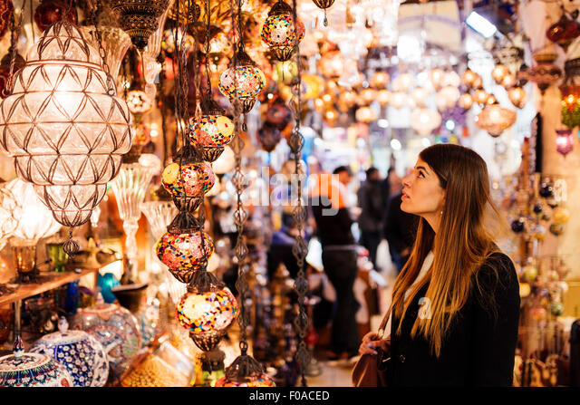 Young woman looking at lights on market stall, Istanbul, Turkey - Stock Image