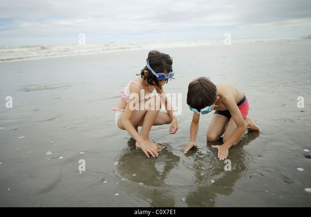 Brother and sister, mixed race, play in the sea. Manawatu, New Zealand. - Stock-Bilder