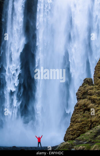 Man with his arms in the air standing at the foot of Skogafoss waterfall, Iceland - Stock Image