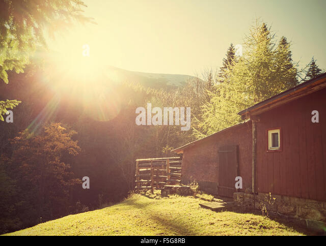 Retro vintage stylized mountain shelter against sun with flare effect. - Stock Image