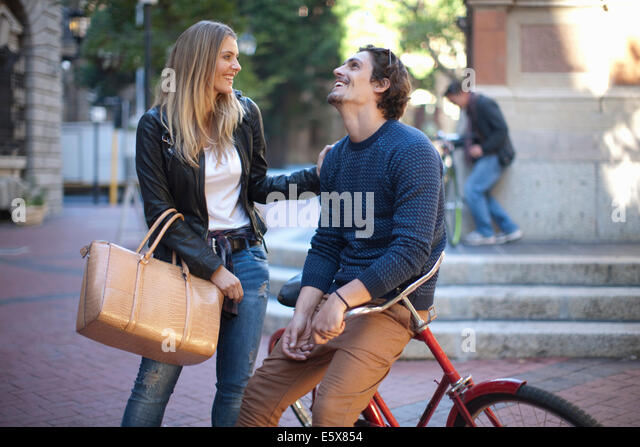 Young woman with boyfriend leaning on bicycle, Cape Town, South Africa - Stock Image