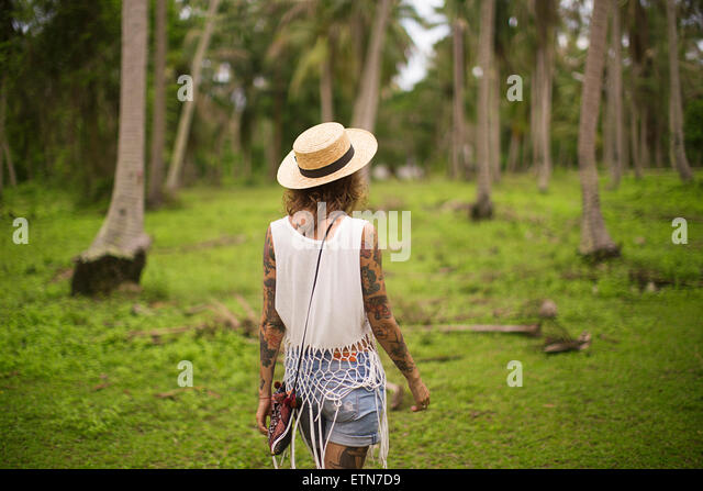 Rear view of a woman walking in a tropical garden, Thailand - Stock Image