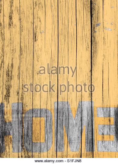 the word Home graffitied on a yellow fence' - Stock Image