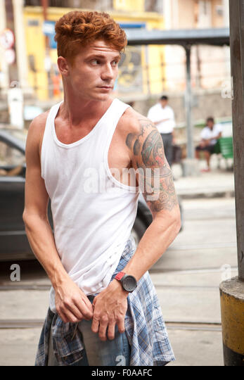 Young man in street, holding pocket of trousers, looking away - Stock Image