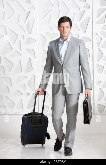 Businessman traveling with briefcase and travel bag - Stock-Bilder
