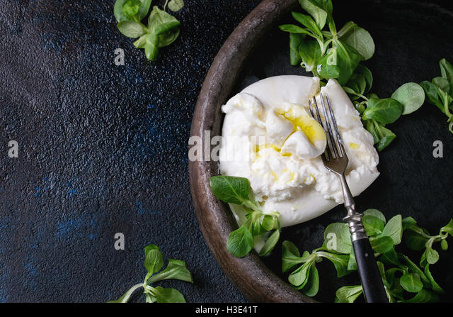 Sliced Italian cheese burrata with vintage fork, fresh corn salad and olive oil in clay tray over dark textural - Stock Image
